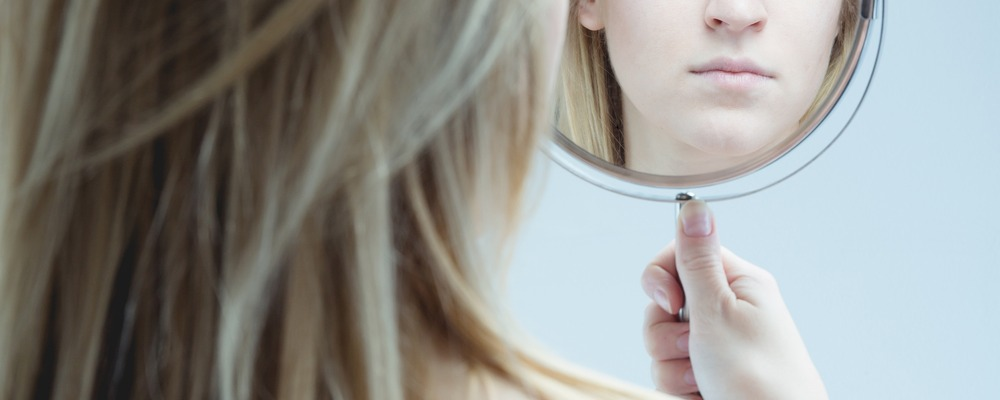 Young pretty girl looking at her reflection in mirror